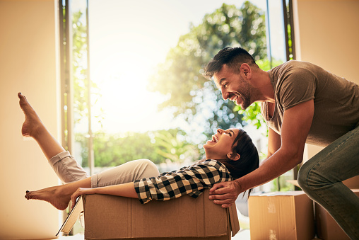 Shot of a young couple having fun while moving into their new place